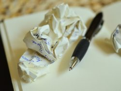 crumpled paper and pen